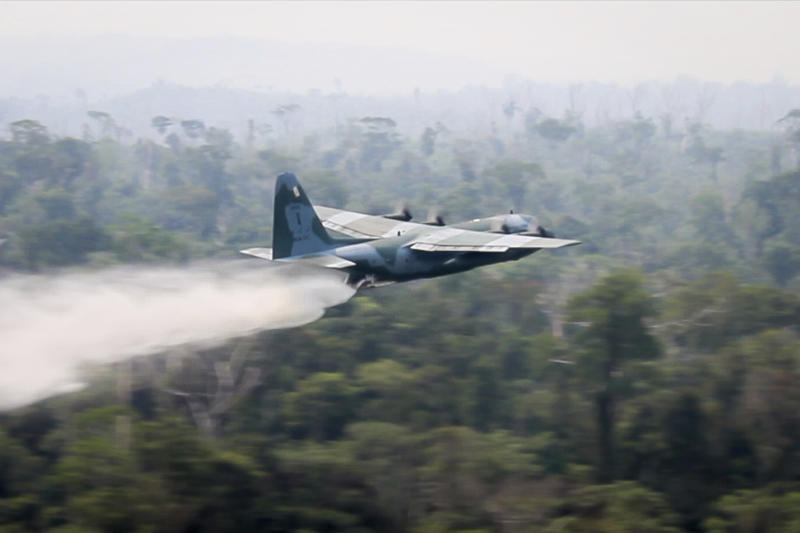 In this photo released by Brazil Ministry of Defense, a C-130 Hercules aircraft dumps water to fight fires burning in the Amazon rainforest, in Brazil, Saturday, Aug, 24, 2019. Backed by military aircraft, Brazilian troops on Saturday were deploying in the Amazon to fight fires that have swept the region and prompted anti-government protests as well as an international outcry. (Brazil Ministry of Defense via AP)