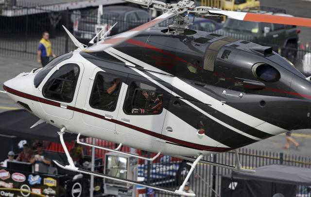 Driver Kurt Busch waves as he arrives in a helicopter for the NASCAR Sprint Cup series Coca-Cola 600 auto race at the Charlotte Motor Speedway in Concord, N.C., Sunday, May 25, 2014. Busch raced in the Indianapolis 500 earlier Sunday. (AP Photo/Gerry Broome)