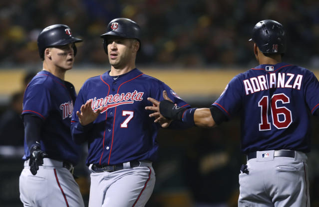 Minnesota Twins' Tyler Austin, left, Joe Mauer (7) and Ehire Adrianza celebrate after scoring against the Oakland Athletics during the sixth inning of a baseball game Friday, Sept. 21, 2018, in Oakland, Calif. All scored on a double by Jorge Polanco. (AP Photo/Ben Margot)