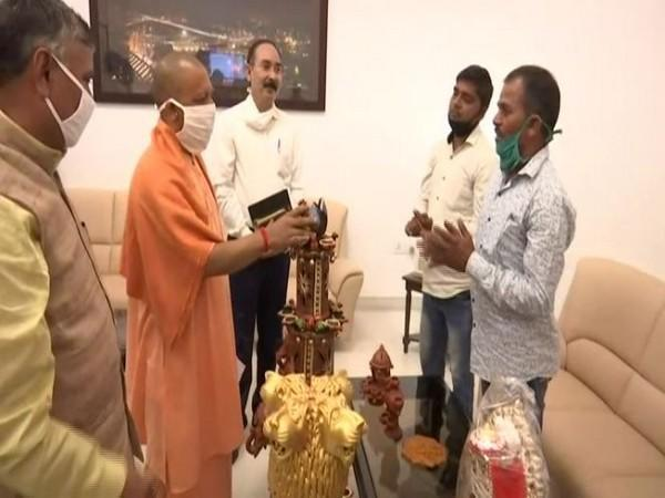 UP Chief Minister Yogi Adityanath with clay artisans at his residence on Friday. (Photo/ANI)