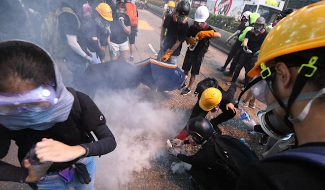 Anti-government protesters try to put out tear gas on Sunday in Tsim Sha Tsui, as demonstrations continue to be characterised by violence from various groups including police, protesters and their opponents. Photo: Felix Wong