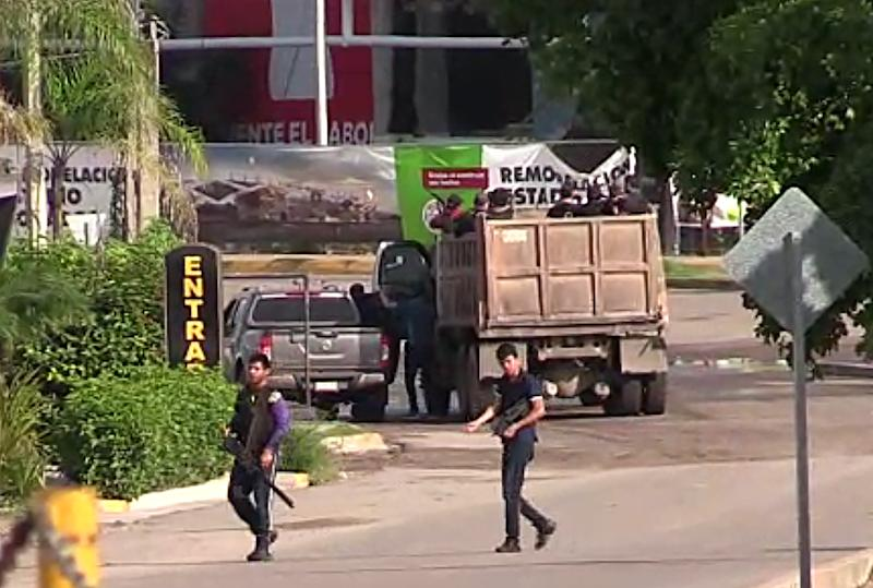"""In this AFPTV screen grab armed gunmen are seen in a street of Culiacan, capital of jailed kingpin Joaquin """"El Chapo"""" Guzman's home state of Sinaloa, on October 17, 2019. - Heavily armed gunmen in four-by-four trucks fought an intense battle against Mexican security forces Thursday in the city of Culiacan, capital of jailed kingpin Joaquin """"El Chapo"""" Guzman's home state of Sinaloa. (Photo by STR / AFP) (Photo by STR/AFP via Getty Images)"""