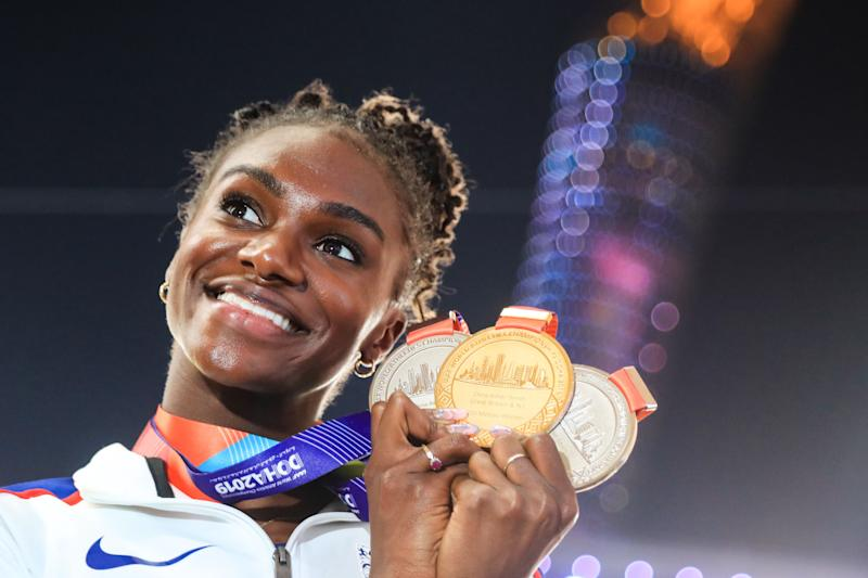 TOPSHOT - Britain's Dina Asher-Smith poses with her gold medal for the Women's 200m, silver medal for the Women's 100m and silver medal for the Women's 4x100m Relay during the medal ceremony at the 2019 IAAF Athletics World Championships at the Khalifa International stadium in Doha on October 6, 2019. (Photo by MUSTAFA ABUMUNES / AFP) (Photo by MUSTAFA ABUMUNES/AFP via Getty Images)