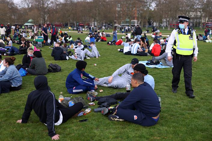 People sit and smoke during a demonstration to mark the informal cannabis holiday, 4/20, in Hyde Park, London, Britain, April 20, 2021. REUTERS/Tom Nicholson