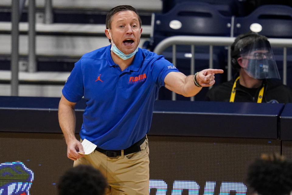 Florida head coach Mike White gestures in the first half of a first round game against Virginia Tech in the NCAA men's college basketball tournament at Hinkle Fieldhouse in Indianapolis, Friday, March 19, 2021. (AP Photo/Michael Conroy)
