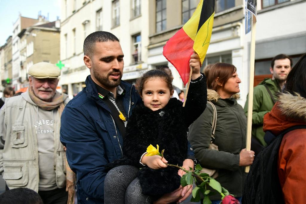 A child carries flowers and a Belgian flag during a commemorative march as Belgium marks the first anniversary of the twin Brussels attacks by Islamic extremists on March 22, 2017 at La Bourse in Brussels (AFP Photo/Emmanuel DUNAND)