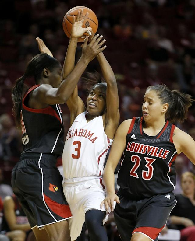 Oklahoma's Aaryn Ellenberg (3) goes between Louisville's Asia Taylor, left, and Shoni Schimmel (23) during the first half of an NCAA college basketball game in Norman, Okla., Sunday, Nov. 17, 2013. (AP Photo/Bryan Terry)