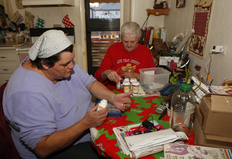 In this Jan. 26, 2011 photo taken in Denver, Sandra Roskilly and her mother Doris Kessler, right, sort out Gregory's medication at home in Denver. Gregory, who has autism and mood disorder, left the Colorado Mental Health Institute at Fort Logan last year when it closed its children's ward because of budget cuts. He now lives at home, where his mother has moved in to help care for him, but she fears Gregory is getting worse without residential treatment. (AP Photo/Ed Andrieski)