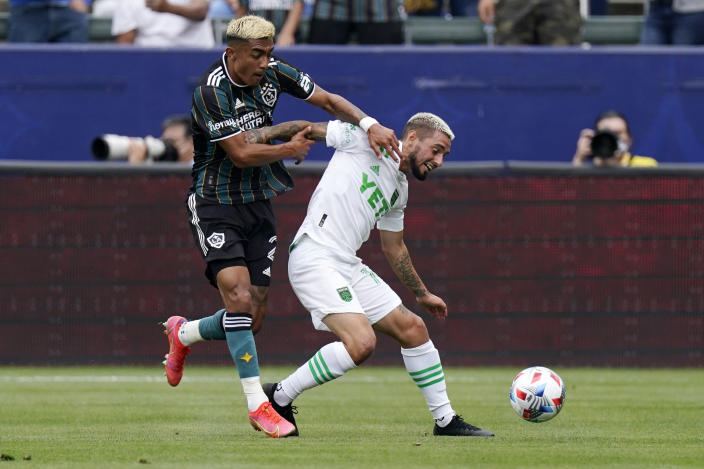 Los Angeles Galaxy defender Julian Araujo, left, and Austin FC forward Diego Fagundez battle for the ball during the first half of a Major League Soccer match Saturday, May 15, 2021, in Carson, Calif. (AP Photo/Mark J. Terrill)