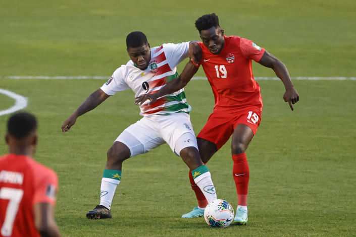 Canada's Alphonso Davies (19) and Suriname's Nigel Hasselbaink (9) work for the ball during the first half of a World Cup 2022 Group B qualifying soccer match Tuesday, June 8, 2021, in Bridgeview, Ill. (AP Photo/Kamil Krzaczynski)