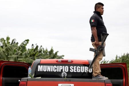 A vigilante stands on the back of a truck while patrolling the municipality of Coahuayana