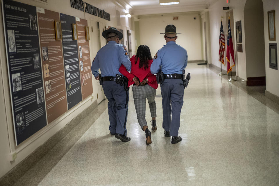 """Rep. Park Cannon (D-Atlanta) is escorted out of the Georgia Capitol by Georgia state troopers after being asked to stop knocking on a door that lead to Gov. Brian Kemp's office while Kemp was speaking after signing a sweeping overhaul of state elections behind closed doors in Atlanta, Thursday, March 25, 2021. An attorney for Cannon says it's """"law enforcement overreach"""" to charge the Georgia House member with two felonies. (Alyssa Pointer/Atlanta Journal-Constitution via AP)"""