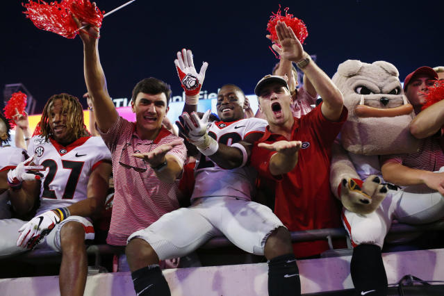 """Georgia defensive back J.R. Reed (20) does the """"gator chop"""" with fans in celebration after after the team's win over Florida in an NCAA college football game Saturday, Nov. 2, 2019, in Jacksonville, Fla. (Joshua L. Jones/Athens Banner-Herald via AP)"""