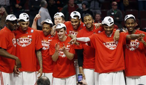 Ohio State players celebrate after an NCAA college basketball game against Wisconsin in the championship of the Big Ten tournament Sunday, March 17, 2013, in Chicago. Ohio State won 50-43. (AP Photo/Charles Rex Arbogast)