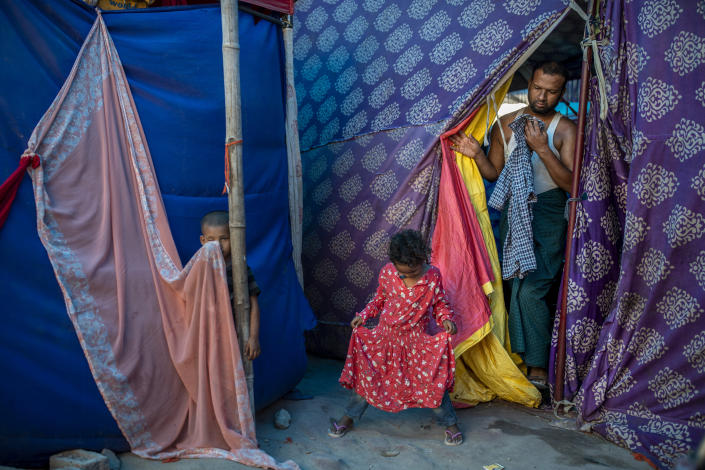 Kids play as Salimullah, 35, a Rohingya refugee comes out of his tent at a refugee camp alongside the banks of the Yamuna River in the southeastern borders of New Delhi, sprawling Indian capital, July 1, 2021. Millions of refugees living in crowded camps are waiting for their COVID-19 vaccines. For months, the World Health Organization urged countries to prioritize immunizing refugees, placing them in the second priority group for at-risk people, alongside those with serious health conditions. (AP Photo/Altaf Qadri)
