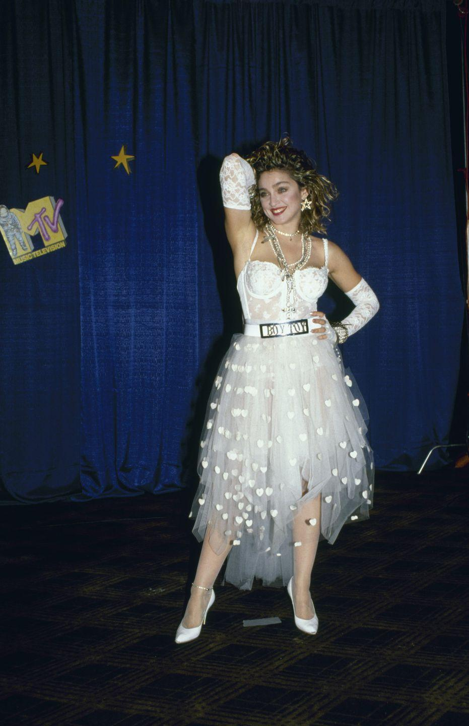 """<p>This bridal lingerie-inspired look is one of Madonna's most iconic style moments of all time. It was especially <a href=""""https://www.yahoo.com/lifestyle/madonnas-like-a-virgin-stylist-recalls-scandalous-1984-vm-as-performance-they-tried-to-destroy-her-that-day-182840304.html?guccounter=1&guce_referrer=aHR0cHM6Ly93d3cuZ29vZ2xlLmNvbS8&guce_referrer_sig=AQAAAGyQyeLyqKsltUy6tqDQSNEgo-FLMBQVt3AvO0qXRbhqIGbAj3u28acH55sFQlHq4uNGdEI9Nh3l2AOunFElqxwu8VETDldTFkAWfXIcx-wZn448IxXA9omQFY4ogJX1viN9BUqfW3OW3sczfCZCVWK_hKDDoagJEkCzR2dMETY8"""" data-ylk=""""slk:scandalous because during her 1984 VMAs performance;outcm:mb_qualified_link;_E:mb_qualified_link;ct:story;"""" class=""""link rapid-noclick-resp yahoo-link"""">scandalous because during her 1984 VMAs performance</a>, she ended up rolling around on the floor and plenty of people got a peek at her undergarments. </p>"""