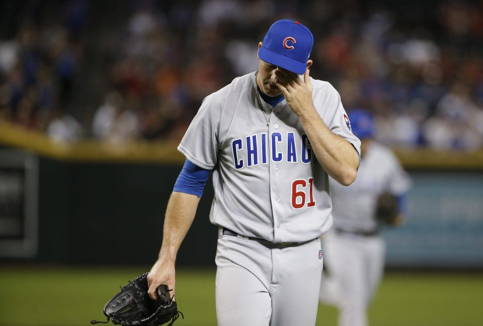Chicago Cubs relief pitcher Allen Webster walks off the field after pitching in the eighth inning of a baseball game, giving up a two-run home run to Arizona Diamondbacks' Jeff Mathis, Wednesday, Sept. 19, 2018, in Phoenix. The Diamondbacks defeated the Cubs 9-0. (AP Photo/Ross D. Franklin)