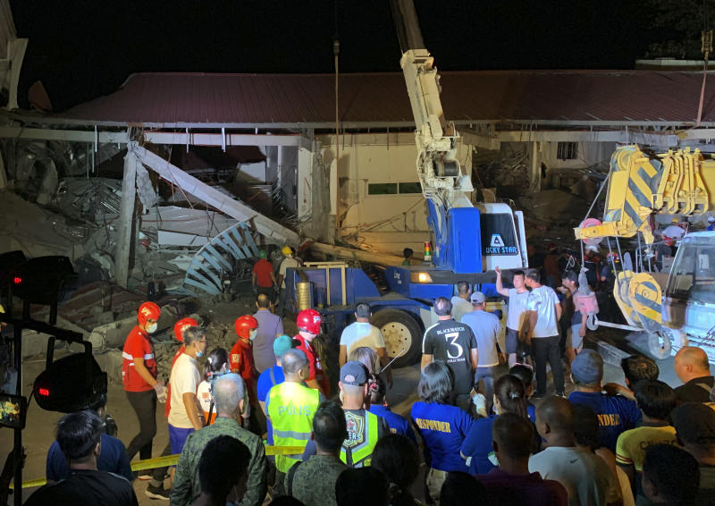 Workers continue rescue efforts on people still trapped inside a collapsed building at Porac town, Pampanga province, northern Philippines Monday, April 22, 2019. A strong 6.1 magnitude earthquake in the north Philippines on Monday trapped some people in a collapsed building, damaged an airport terminal and knocked out power in at least one province, officials said. (AP Photo/Bullit Marquez)