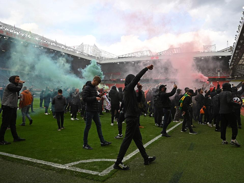 Fans set off flares on the pitch at Old Trafford before the game with Liverpool was called offAFP via Getty Images