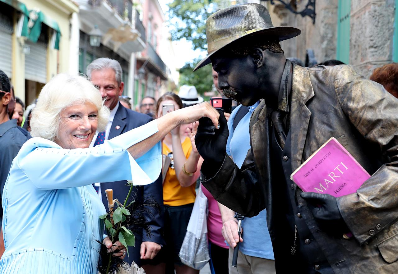 <p>Camilla receives a kiss on the hand from a human statue during a guided tour of Old Havana in Cuba [Photo: Getty] </p>