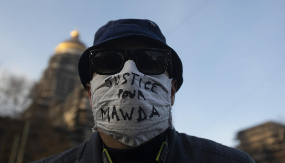 FILE - In this Monday, Nov. 23, 2020 file photo, a man wears a protective face mask as he attends a solidarity event for Mawda Shawri at the courthouse in Brussels. A police officer was handed a one-year suspended prison sentence Friday, Feb. 12, 2021 following the shooting death of a two-year-old toddler who was in a van during a high-speed chase between police and suspected migrant smugglers seeking to get to Britain. (AP Photo/Virginia Mayo)