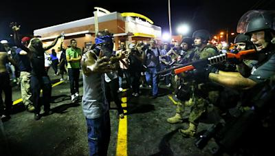 Police officers move in to arrest protesters as they push and clear crowds out of the West Florissant Avenue area in Ferguson, Mo. early Wednesday, Aug. 20, 2014. On Aug. 9, 2014, a white police officer fatally shot Michael Brown, an unarmed black 18-year old, in the St. Louis suburb. (AP Photo/Atlanta Journal-Constitution, Curtis Compton)