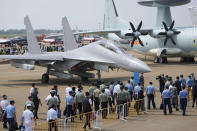 Invited guests and military officers walk past the J-16D on display during the 13th China International Aviation and Aerospace Exhibition, also known as Airshow China 2021, on Tuesday, Sept. 28, 2021, in Zhuhai in southern China's Guangdong province. The PLA's air force displayed the J-16D electronic warfare airplane for the first time, according to the official China News Service. (AP Photo/Ng Han Guan)