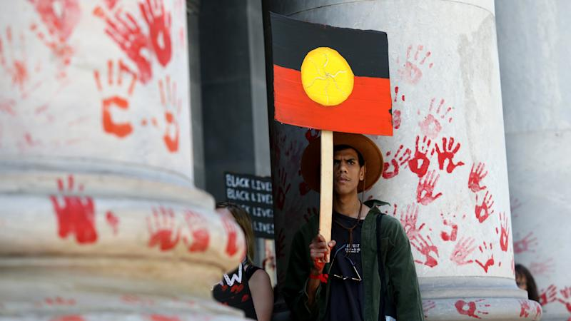 Protestors leave red paint hand prints on a pillar during a protest outside the South Australian Parliament in Adelaide, Wednesday, November 13, 2019. Aboriginal and Torres Strait Islander communities and allies are calling for justice for 19-year-old Warlpiri teenager Kumanjayi Walker, who died after being shot by police on Saturday night in the central desert town of Yuendumu in the Northern Territory. (AAP Image/Kelly Barnes) NO ARCHIVING