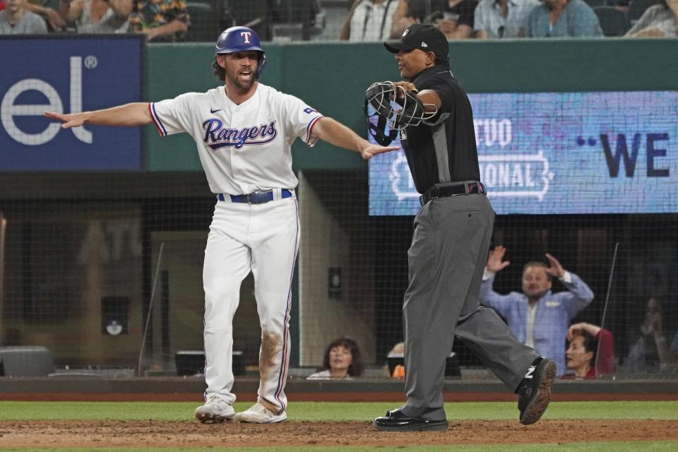 Texas Rangers base runner Charlie Culberson signals himself safe at home as he scores a run against the Seattle Mariners in the eighth inning of a baseball game Saturday, May 8, 2021, in Arlington, Texas. (AP Photo/Louis DeLuca)