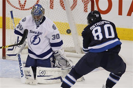Tampa Bay Lightning's goaltender Dwayne Roloson (30) saves the shot from Winnipeg Jets' Nik Antropov (80) during second-period NHL hockey game action in Winnipeg, Manitoba, Saturday, April 7, 2012. (AP Photo/The Canadian Press, John Woods)