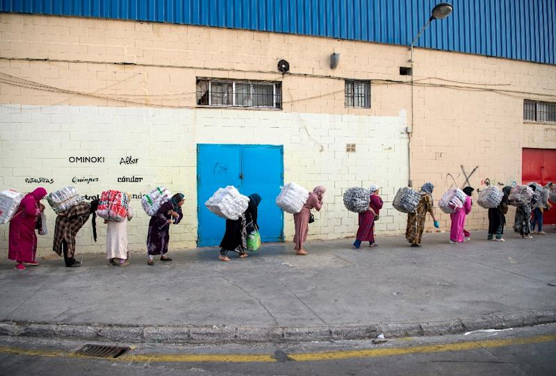 Female Moroccan porters carry bundles of goods on their backs to transport across the El-Tarajal border from Spain's North African exclave of Ceuta into Morocco (AFP Photo/FADEL SENNA)