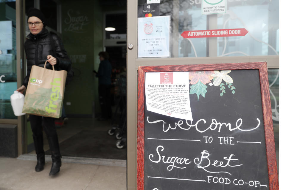 A shopper at the Sugar Beets Food Co-Op in the Village of Oak Park, Ill., leaves the store during a time frame dedicated to older shoppers Friday, March 20, 2020. There are at least three confirmed cases of COVID-19 in Oak Park, just nine miles from downtown Chicago, where the mayor has ordered residents to shelter in place. With so few tests available, surely there are others, says Tom Powers, spokesman for the village of about 52,000 in a metropolitan area with millions. (AP Photo/Charles Rex Arbogast)