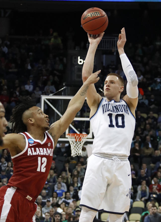 Villanova 's Donte DiVincenzo (10) sinks a 3-point shot over Alabama 's Dazon Ingram (12) during the first half of an NCAA men's college basketball tournament second-round game, in Pittsburgh, Saturday, March 17, 2018. (AP Photo/Gene J. Puskar)