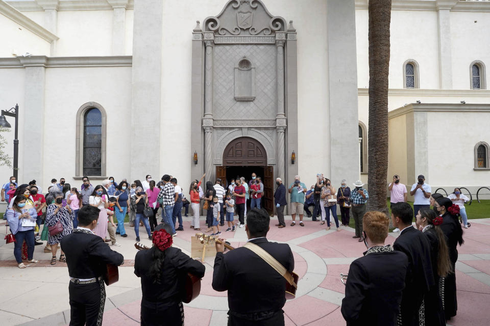 After morning Mass, Mariachi band Los Changuitos Feos (Ugly Little Monkeys) preform for parishioners outside in the courtyard of St. Augustine Cathedral Sunday, Aug. 18, 2021 in downtown Tucson. For the hundreds of worshipers gathered in this Spanish colonial church, and other congregations across the Southwest, the unique sound of mariachi liturgy is more than just another version of choir. It evokes a borderlands identity where spirituality and folk music have blended for centuries. (AP Photo/Darryl Webb)