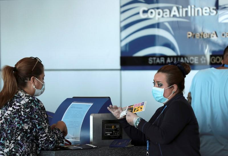A Copa Airlines employee, wearing a protective mask, talks to a passenger at Tocumen International Airport after the Panamanian government restricted flights in recent days due to the coronavirus disease (COVID-19) outbreak, in Panama City