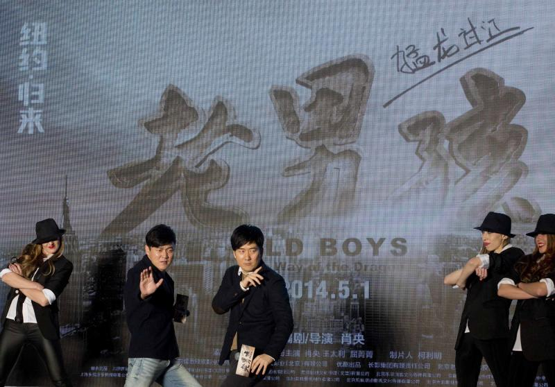 """Chinese film director and actor Xiao Yang, second from left, and actor Wang Taili, center, pose with the dancers on stage as they promote their new movie """"Old Boys: The Way of the Dragon"""" in Beijing Thursday, Jan. 9, 2014. An online microfilm that was watched by millions and helped to establish a genre in China is to be made into a feature-length movie and shown in the country's cinemas. The planned debut of """"Old Boys"""" in China's cinemas in May after ratcheting up almost 70 million views on a video website demonstrates how online films are influencing the traditional film industry. (AP Photo/Andy Wong)"""