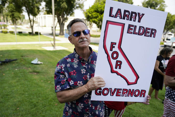 A supporter of Conservative radio talk show host Larry Elder listens during a campaign stop by Elder, Tuesday, July 13, 2021, in Norwalk, Calif. Elder announced Monday that he is running for governor of California. (AP Photo/Marcio Jose Sanchez)