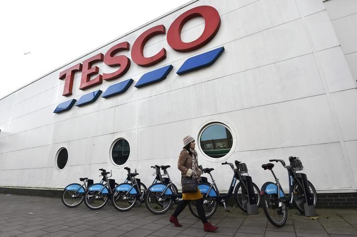 FILE PHOTO: Woman walks past a Tesco supermarket in central London
