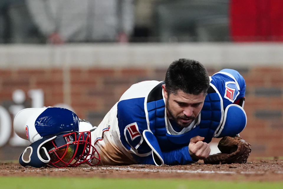Atlanta Braves catcher Travis d'Arnaud (16) lies on the ground after Philadelphia Phillies' Alec Bohm scored the go-ahead run in the ninth inning of a baseball game Sunday, April 11, 2021, in Atlanta. (AP Photo/John Bazemore)