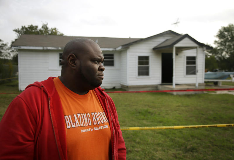 Terrence Walker of Forney, Texas, the brother of 36-year-old Charles Everett Brownlow Jr., stands in front of their mother, Mary Brownlow's house as he answers a reporters question, Tuesday, Oct. 29, 2013, in Terrell, Texas. Police arrested Charles Everett Brownlow Jr. early Tuesday who is suspected of killing five people, including his mother, during a series of attacks hours earlier in his rural North Texas community. Mary Brownlow,was found dead Monday evening in the house where a fire was set and very clearly an arson, according to authorities. (AP Photo/Tony Gutierrez)