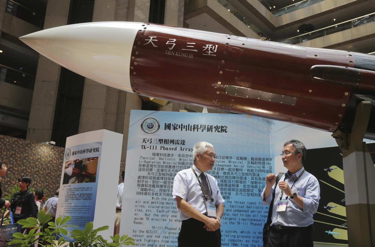 "FILE - In this Aug. 13, 2015, file photo, two men speak under the Taiwan-made ""Tien-Kung III"" surface to air missile during the 2015 Taipei Aerospace and Defense Technology Exhibition in Taipei, Taiwan. Taiwan is responding to China's defense buildup by developing missiles and interceptors of its own that could reduce Beijing's military advantage over the island, defense experts say. (AP Photo/Wally Santana, File)"
