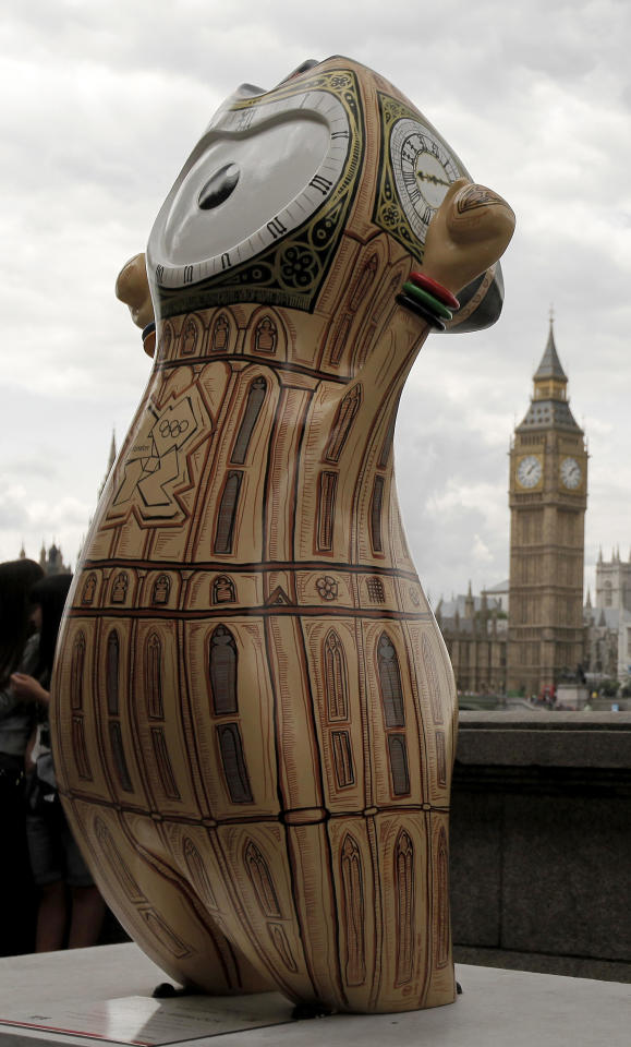 An Olympic mascot, painted in the likeness of Big Ben, is displayed across the River Thames from the actual Big Ben on Saturday, July 21, 2012, in London. The statue is one of 84 fiberglass sculptures of the mascots Wenlock or Mandeville that were painted by various artists and erected across the city for the 2012 London Olympic Games. (AP Photo/Charlie Riedel)