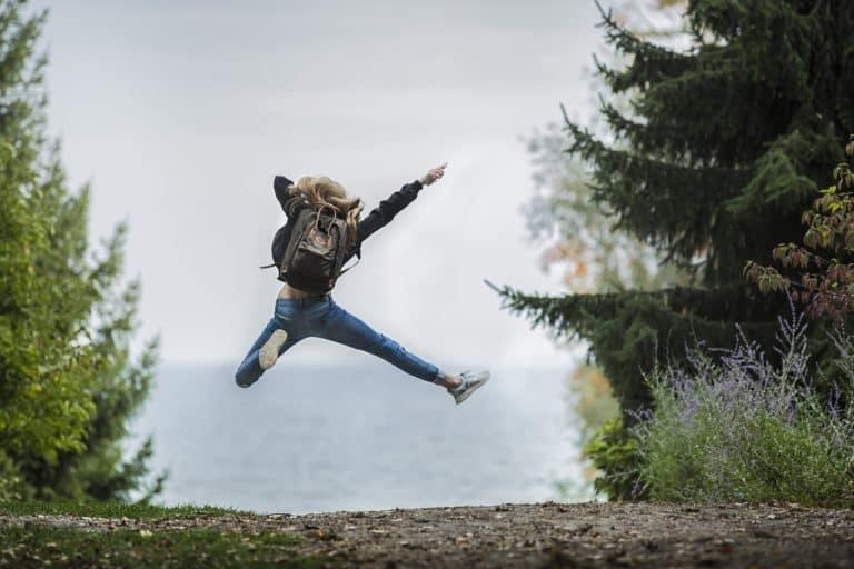 Happy woman jumping in forest
