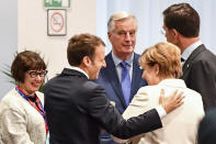 FILE - In this Friday, Oct. 20, 2017 file photo, French President Emmanuel Macron, second left, speaks with German Chancellor Angela Merkel, second right, and European Commission's Head of Task Force for Relations with the United Kingdom Michel Barnier, center, prior to a round table meeting at an EU summit in Brussels. He's known throughout most of Europe as Mr. Brexit, but not so well known at home in France. With a new book out this week, and interviews in national media, Michel Barnier is trying to raise his profile ahead of next April's presidential election. (AP Photo/Geert Vanden Wijngaert, File)