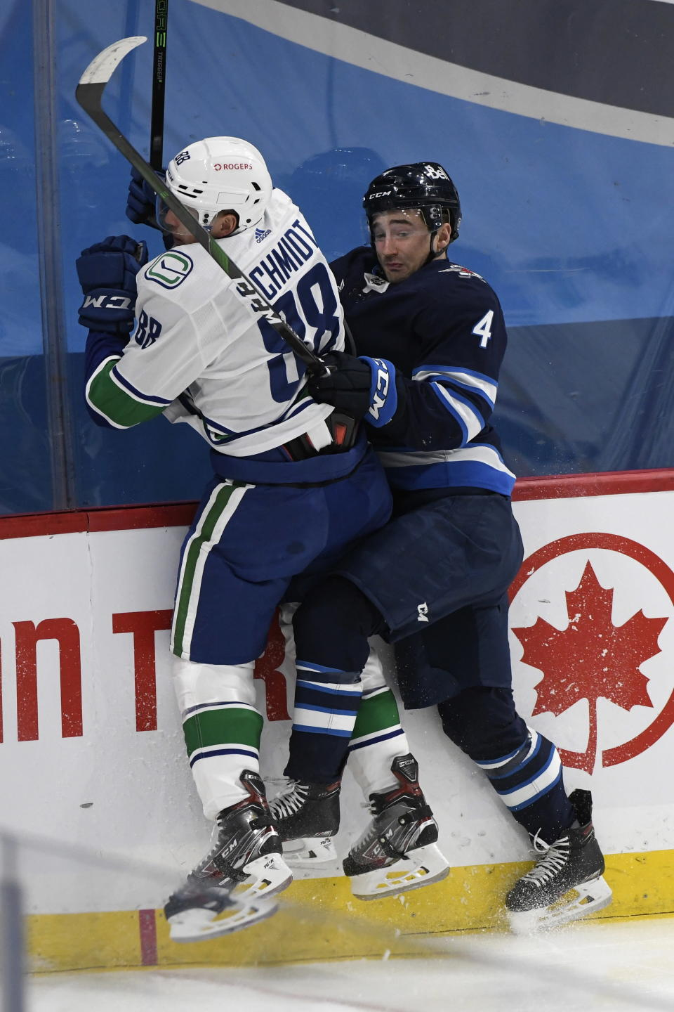 Winnipeg Jets' Neal Pionk (4) checks Vancouver Canucks' Nate Schmindt (88) during first period NHL hockey action in Winnipeg, Manitoba on Tuesday March 1, 2021. (Fred Greenslade/The Canadian Press via AP)