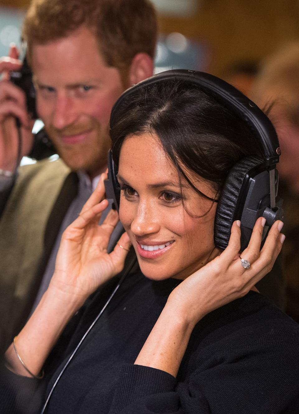 Britain's Prince Harry and his fiancée US actress Meghan Markle listen to a broadcast through headphones during a visit to Reprezent 107.3FM community radio station in Brixton, south west London on January 9, 2018.   / AFP PHOTO / POOL / Dominic Lipinski        (Photo credit should read DOMINIC LIPINSKI/AFP via Getty Images)