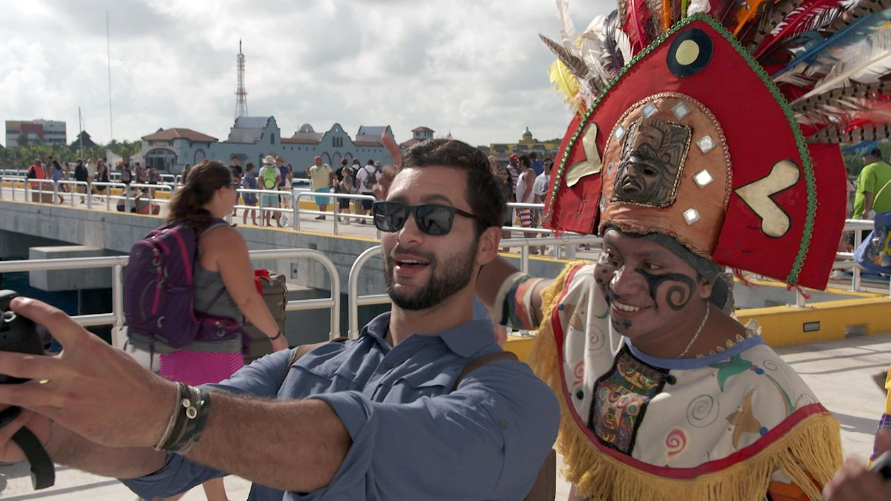 """This undated photo provided by Carnival Corporation shows Josh Garcia in Playa del Carmen, Mexico, taking a selfie with a local resident dressed in costume to greet cruise passengers in a scene from a new show airing on NBC this fall called """"The Voyager with Josh Garcia."""" The show is one of three new shows produced by Carnival Corp., showcasing vacation and travel connected to cruising. Josh Garcia hosts the show, which explores the history and culture of various ports through meetings with locals. (Carnival Corporation via AP)"""
