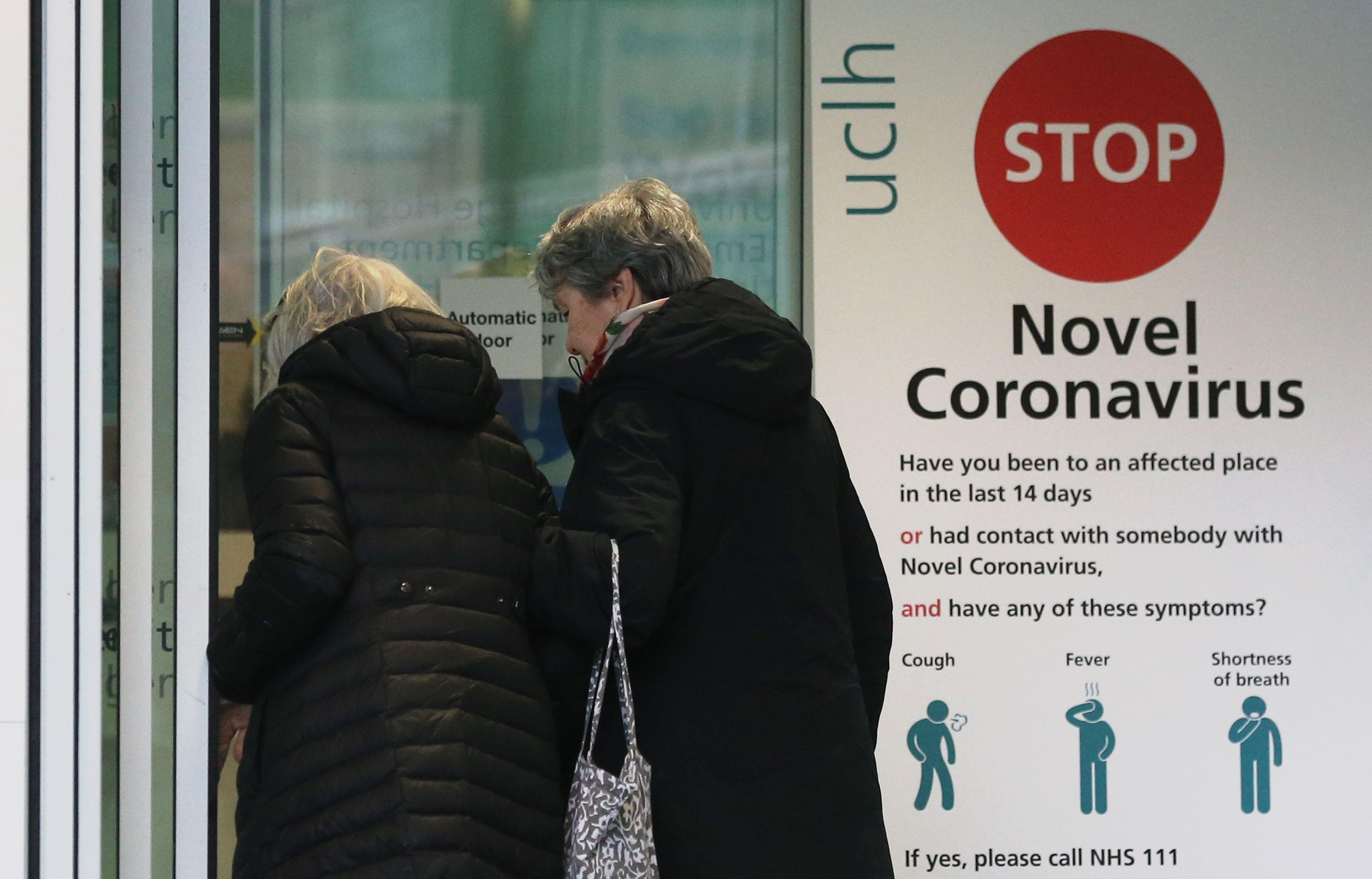 Two women walk past a sign providing guidance information about novel coronavirus (COVID-19) at one of the entrances to University College Hospital in London on March 5, 2020. - The number of confirmed cases of novel coronavirus COVID-19 in the UK rose to 85 on March 4, with fears over the outbreak delaying the global release of the new James Bond movie and causing lack of demand for air travel that has proved the final nail in the coffin for British regional airline Flybe which went into administration on March 5. (Photo by Isabel Infantes / AFP) (Photo by ISABEL INFANTES/AFP via Getty Images)