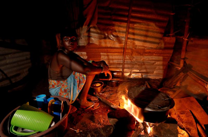 "Maria Jofresse cooks in her makeshift shelter in the aftermath of Cyclone Idai, April 4, 2019. Jofresse lost her two children to the storm. ""People suffered indeed, but no one suffered as I did because I lost the most precious things I had — my kids,"" she said. (Photo: Zohra Bensemra/Reuters)"