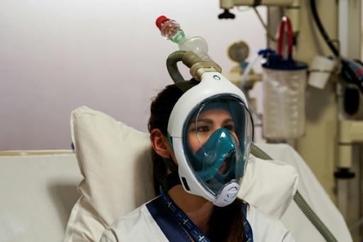A medical worker tests a Decathlon snorkeling mask, with a 3D-printed respiratory valve fitting attached, at the Erasme Hospital in Brussels